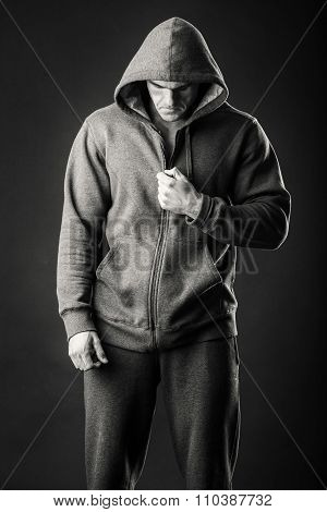 An athlete in a sports jacket with a hood on a dark background.