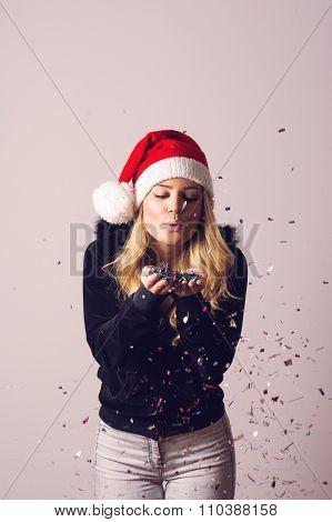 Happy teenage girl blowing confetti
