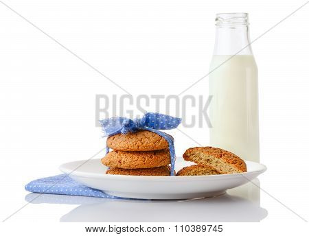 Stack of three homemade oatmeal cookies and halves of cookies on plate and glass of milk