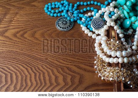 Placer Jewelry And Ornaments On The Wooden Table