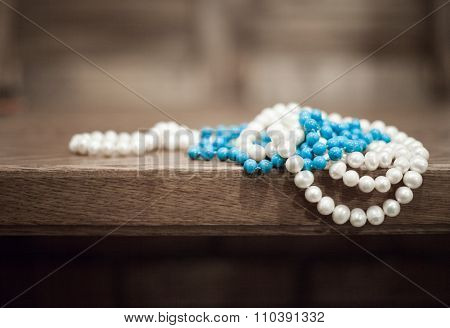 Pearls And Turquoise Beads Hang From The Edge Of The Table