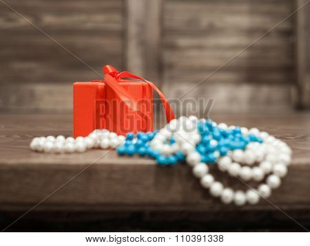 A Gift In A Red Box And Pearls, Turquoise Beads Hang From The Edge Of The Table