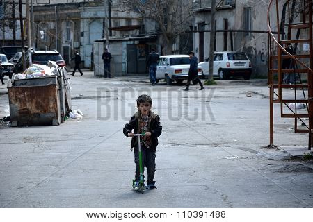 Young boy on a scooter in Sovietskaya, a poor part of Baku, Azerbaijan
