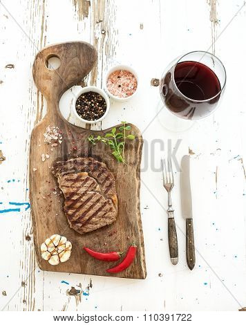 Grilled ribeye beef steak with herbs, spices  and glass of red wine on walnut cutting board over whi