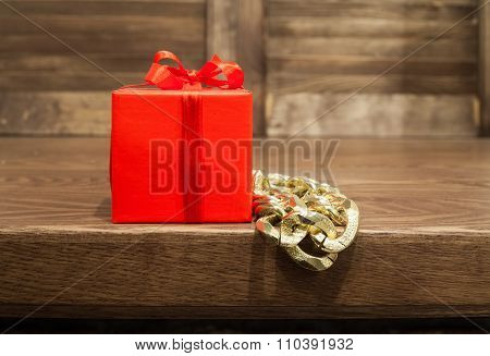 Gift In Red Box And P Metal Beads Hang From The Edge Of Table