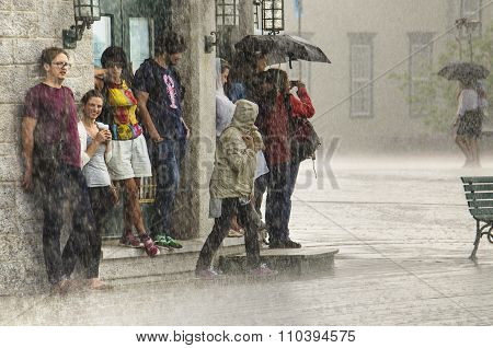 A group of people hide from heavy rain under a building.