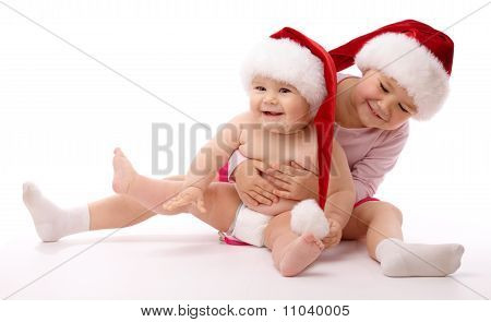 Two Children Wearing Red Christmas Caps And Smile