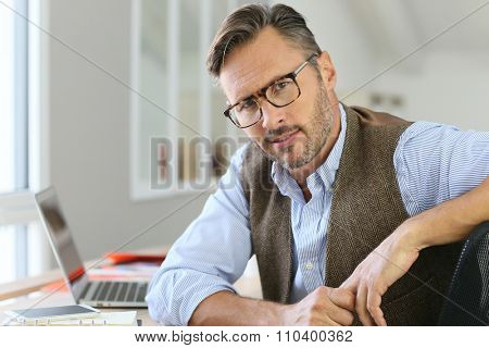 Handsome man with eyeglasses sitting in office