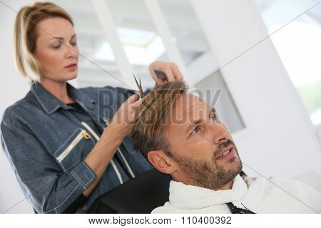 Middle-aged man having a haircut at hairdressing salon