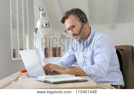 Businessman teleworking, headset on