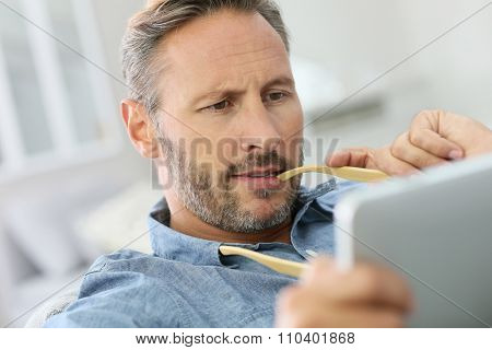 Man relaxing in sofa and using pad