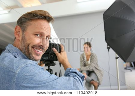 Photographer on a shooting day in studio with model