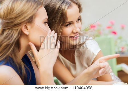 people, communication and friendship concept - smiling young women gossiping at outdoor cafe
