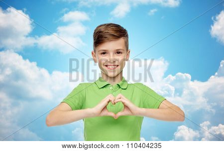 childhood, love, charity, health care and people concept - happy smiling boy in green polo t-shirt showing heart hand sign over blue sky and clouds background