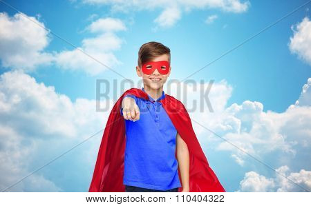 childhood, gesture, carnival costume and people concept - happy boy in red superhero cape and mask pointing finger to you over blue sky and clouds background