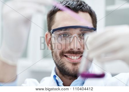 science, chemistry, technology, biology and people concept - young scientist mixing reagents from glass flasks and making test or research in clinical laboratory