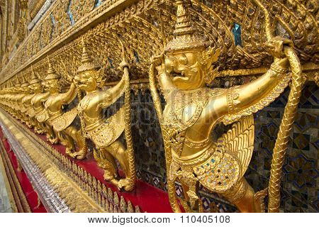 Golden Garuda statues along wall n Bangkok