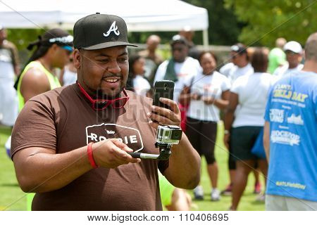 Man Uses Smart Phone To Operate GoPro Camera At Event