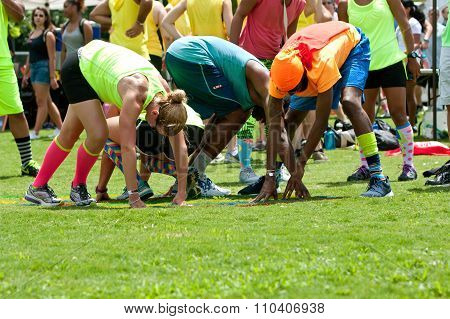 Young Adults Bend And Stretch Playing Grass Twister