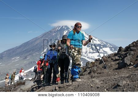 Group Of Tourists Go Hiking And Climbing To The Top Of Volcano