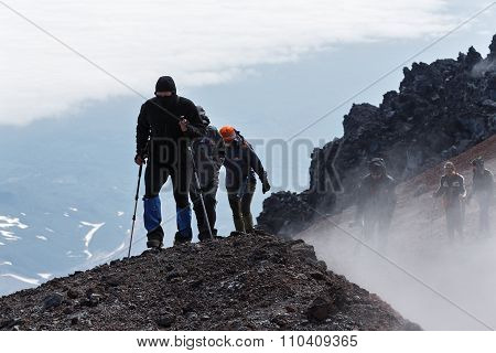 Group Of Tourists Climbing To Top Crater Of Active Volcano