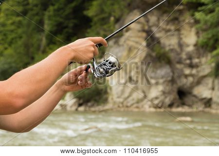 Trout fishing in a mountain river. Sport fishing.