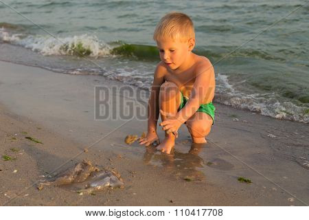 A young boy walks along the beach.