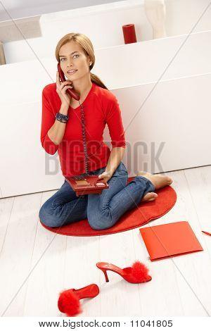 Junge weibliche Gespräch am Telefon im roten Pullover