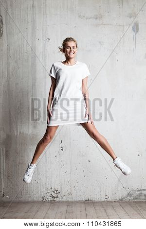 Young Woman With A Smile Wearing A White T-shirt Jumps