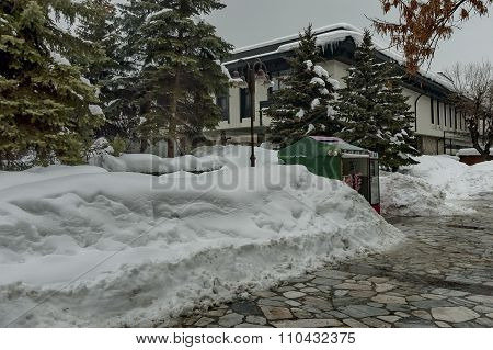 Snow winter square in the Bansko town with beauty ancient house
