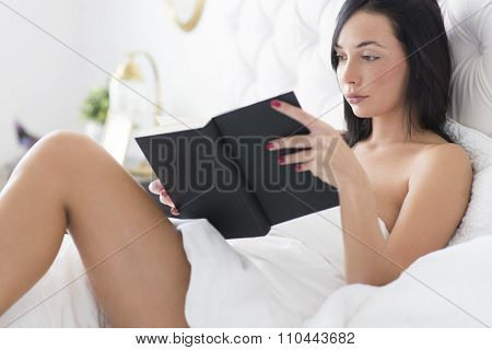 Young Woman Reading Book  In The Bed