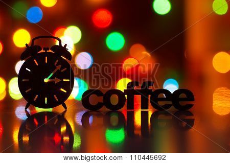 Silhouette Of Alarm Clock And Inscription Of Coffee With Garland Lights On Background. Concept