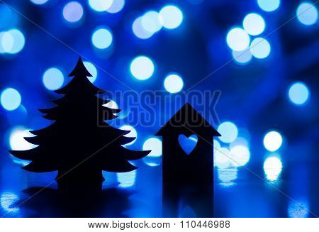 Silhouette Of House With Hole In Form Of Heart And Big Christmas Tree With Blue Garland Lights On Da