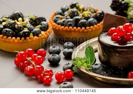 Tarts With Blueberries, Red Currants And Chocolate On The Table