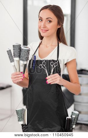 Attractive female hairstylist is working at beauty salon