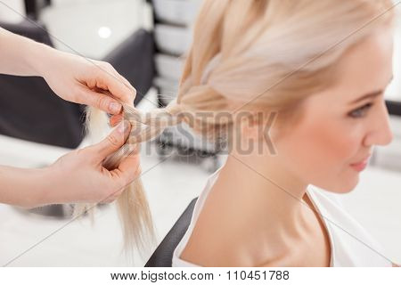 Cheerful hairdresser is braiding human blond hair