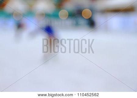 Abstract blur image of ice skater on skating rink.