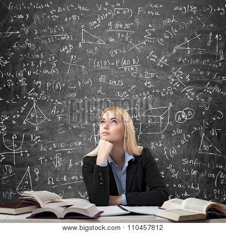 Woman Sitting At The Desk With Books Around Thinking Education