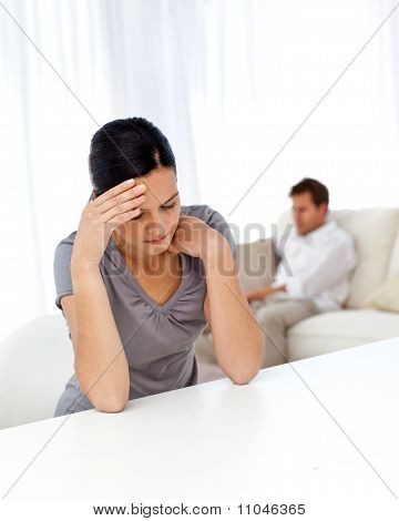 Worried Woman Sitting At A Table While Her Boyfriend Is Lying On The Sofa