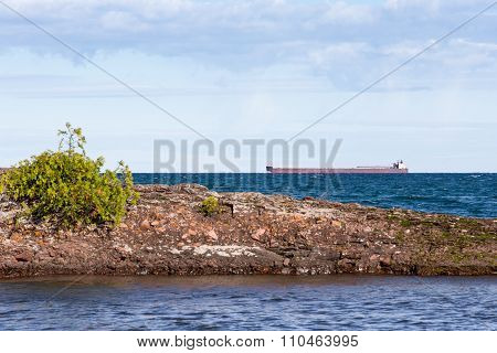 Great Lakes Freighter Passing Behind A Rocky Island