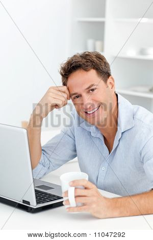 Portrait Of Man Drinking Coffee While Working On His Laptop