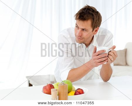 Pensive Man Drinking Coffee Standing At A Table