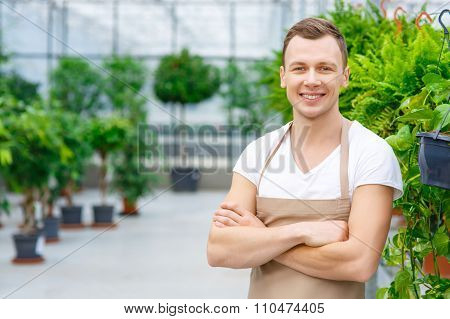Young cheerful florist inside the greenhouse.