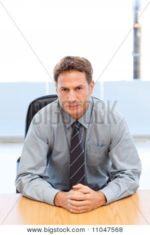 Confident Manager Posing Alone At A Table