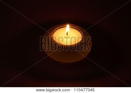 burning tea candle in a small marble candle holder