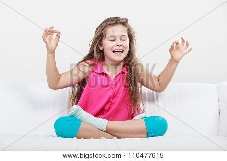 Funny Happy Little Girl Sitting On Sofa Meditating