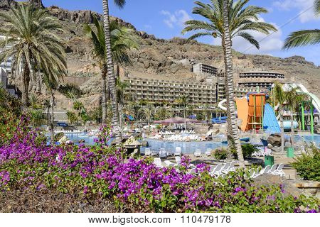 TAURITO - NOVEMBER 26: Tourists enjoy the sunny weather and relaxing on the Lago Taurito Parque Acuatico on 26 November 2015 in Taurito, Gran Canaria Island.