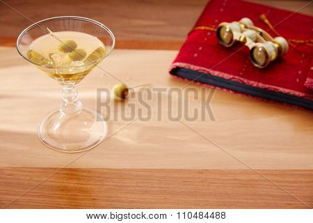 white vermouth cocktail with vintage binoculars on red folder