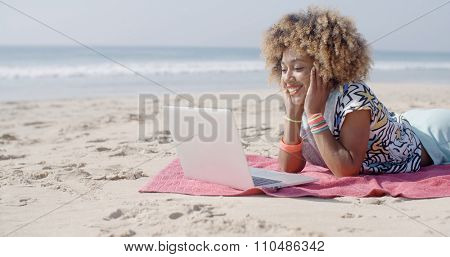 Woman on the beach using a computer with the sea in the background