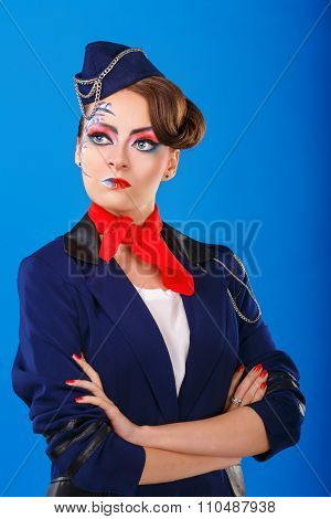 Stewardess With Face Art Posing With Folded Arms.